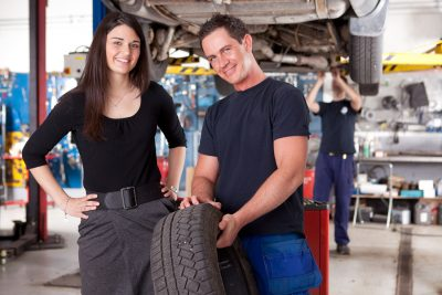 Auto repair mechanic with customer and tire - automotive management training